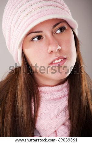 winter portrait of a beautiful young woman with a cap and a scarf - stock photo
