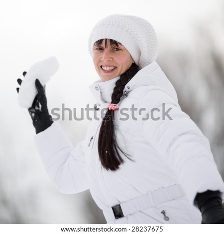 Winter portrait of a happy playful girl with a snowball in her hand - Shallow DOF - stock photo