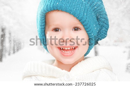 winter portrait of a little happy baby child girl in hat - stock photo