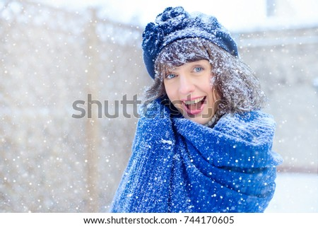 Winter portrait of a  woman. Beauty Joyous Model Girl touching her face skin and laughing, having fun in the winter park. Beautiful young woman laughing outdoors. Enjoying nature, in winter and snow.
