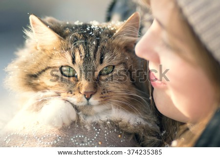 Winter portrait of a woman with a cat - stock photo