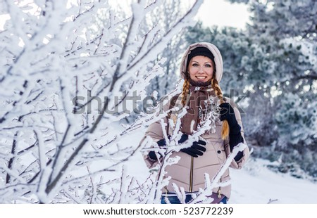 Winter portrait of a yong girl at the snow forest. Snow lanscape at the top of a mountain