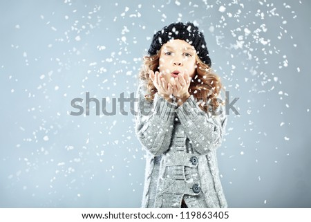 Winter portrait of cute little girl wearing warm cozy clothes studio shot with snow - stock photo