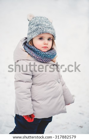 winter portrait of cute toddler girl on the walk - stock photo