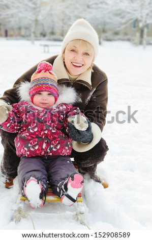 Winter portrait of grandmother and granddaughter on sleight - stock photo