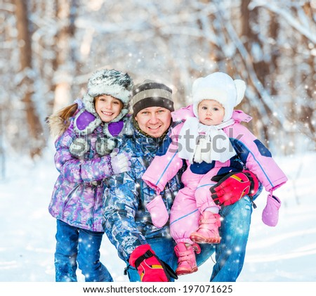 Winter portrait of happy young family of 3 people - stock photo