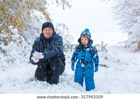 Winter portrait of kid boy and father in colorful clothes, outdoors during snowfall. Active outoors leisure with children in winter on cold snowy days. Happy man and son having fun with snow in forest - stock photo