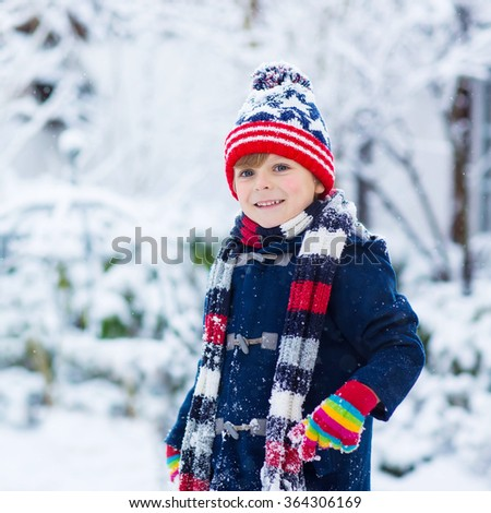 Winter portrait of kid boy in colorful clothes, outdoors during snowfall. Active outoors leisure with children in winter on cold snowy days. Happy child having fun with snow - stock photo