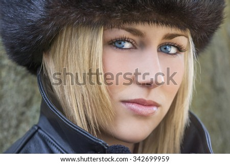 Winter portrait of naturally beautiful woman in her twenties with blond hair, perfect teeth  and blue eyes wearing fur hat gloves and leather coat - stock photo