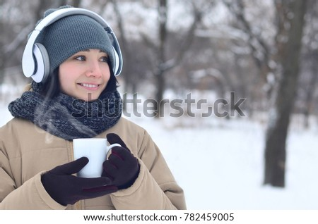 Winter portrait of pretty attractive caucasian pierced girl in snowy wood. She is listening to music on big white headphones with coffee cup in her hands. Walks in the open air