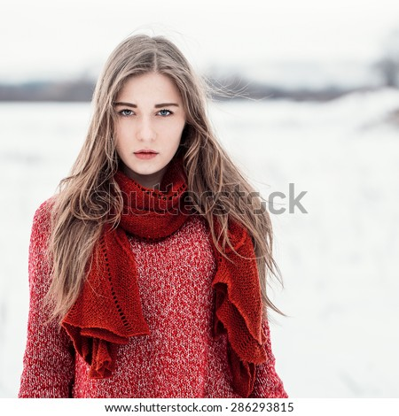 winter portrait of serious cute beautiful attractive young girl with long light hair with striped black and white jacket and scarf on natural winter background in field. Outdoor photo - stock photo