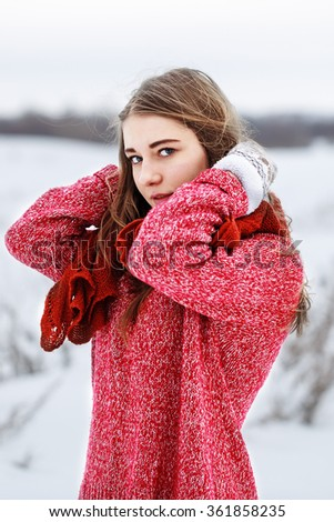winter portrait of young cute blond girl with red sweater and scarf looking to camera and fixing hair on gray natural cloudy background. Outdoor winter photo in field - stock photo