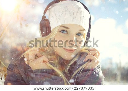 Winter portrait of young girl with headphones music - stock photo