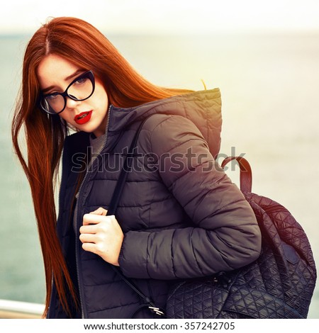Winter portrait of young stunning traveler woman, posing near sea at lonely beach, red lips, neon hat, warm coat, backpack, street style outfit, rainy windy cold weather, hipster style. vintage colors - stock photo