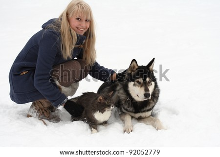 winter portrait of young woman with her cat and Eskimo dog on white background - stock photo