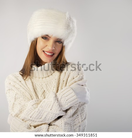 Winter portrait. Woman wearing fur cap and knitted sweater: