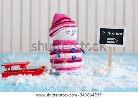 Winter rest or ski resort concept. Snowman with red sled stand near direction sign To the top. Postcard. - stock photo