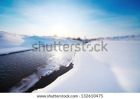 Winter river with ice on a surface and snowy coast under blue clear sky - stock photo