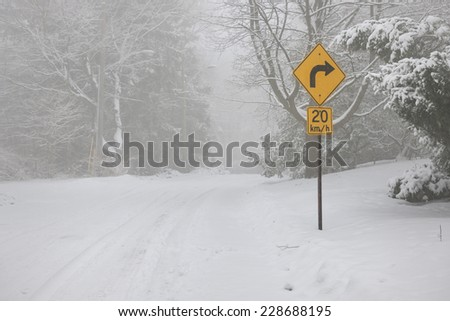 Winter road covered with thick snow and yellow speed limit sign. Toronto, Canada. - stock photo