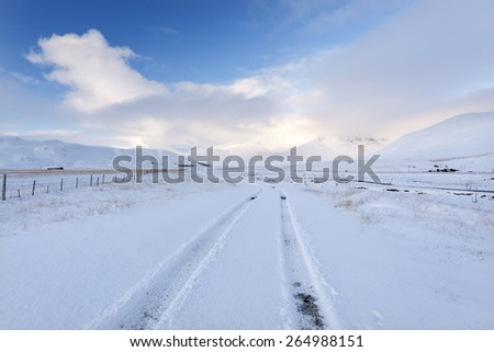 Winter road in Iceland surrounded by snow mountains/ Winter Road - stock photo