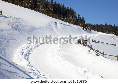 Winter road in mountains in Carpathians - stock photo
