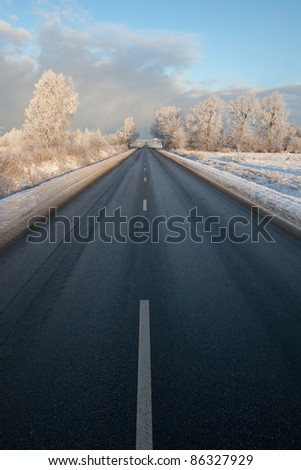 Winter road in very cold winter morning with frosty tree - stock photo