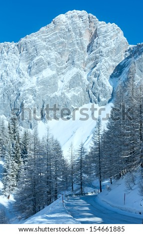 Winter rock with fresh fallen snow on top and and alpine road. - stock photo