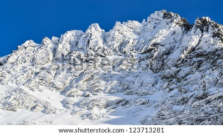 Winter rocky mountain peak with blue sky background, High Tatras, Slovakia - stock photo