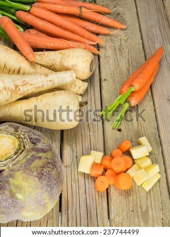 winter root crops  against aged wooden background with peeled and sliced vegetables