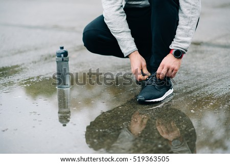 Winter running and sport concept. Man lacing footwear and getting ready for fitness workout under the rain.