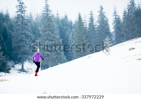 Winter running woman. Sport, fitness, jogging inspiration and motivation. Young happy woman cross country running in mountains on snow, winter day. Female trail runner working out, jogging exercising. - stock photo