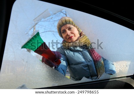 Winter scene, adult woman scraping ice from windshield of car - stock photo