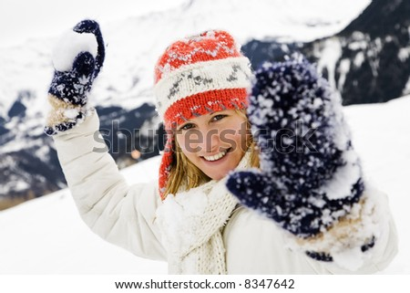 winter scene: girl playing with snowballs - stock photo