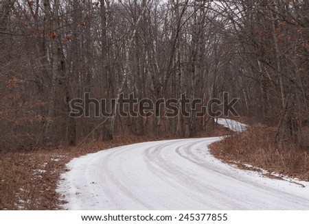 Winter scene: icy white road curving through the woods - stock photo