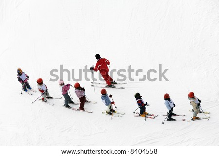 winter scene: kids learning to ski and their instructor - stock photo