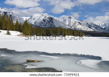 Winter scene of Johnson Lake, located in Banff National Park, Alberta, Canada Frozen over and accessable for snow shoeing and ice fishing - stock photo