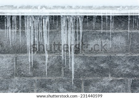 Winter scene of long icicles hanging against brick wall - stock photo