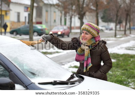 Winter scene, smiling mature adult woman cleaning snow from windshield of car using broom - stock photo
