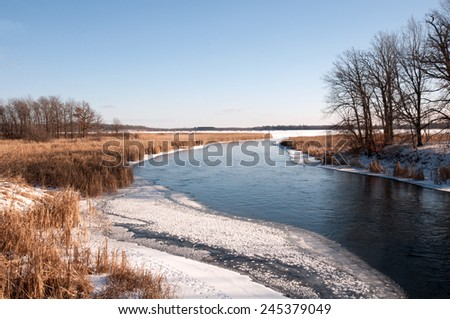 Winter scenery: partly frozen river channel - stock photo