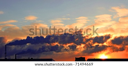 Winter scenic of power plant with a burning red sky behind - stock photo