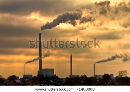 Winter scenic of power plant with a burning yellow sky behind - stock photo