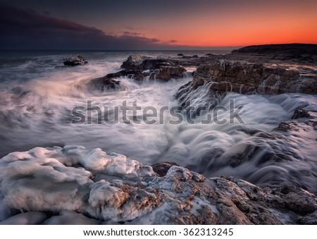 Winter sea. Magnificent sunset view of a stormy winter Black sea near Tulenovo, Bulgaria. - stock photo