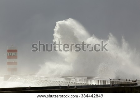 Winter seascape with stormy waves over pier and beacon in the middle of spray and moisture. Interesting light coming from a light beam of an overcast sky before rain. - stock photo
