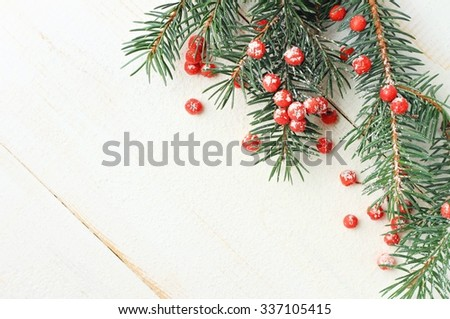 Winter season festive white wooden background decorated frame natural green fir tree twigs and bright red berries, empty space.  - stock photo