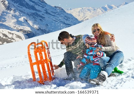 Winter season. Happy family having fun on fresh snow on vacation. - stock photo