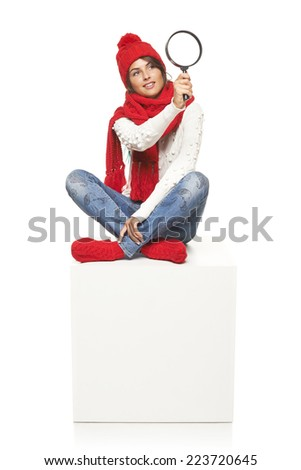 Winter seasonal search. Surprised woman wearing knitted warm red scarf, hat and socks sitting on blank billboard placard sign, looking through magnifying glass - stock photo
