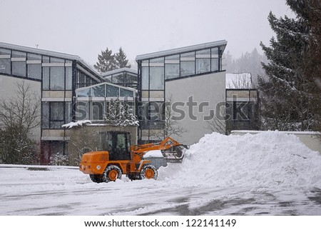 Winter Services - Wheel loader clears place of snow. - stock photo