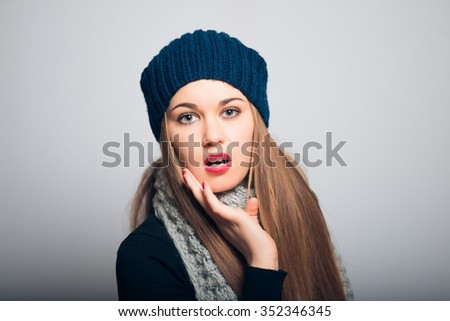 Winter shocked surprise. Lifestyle studio photo isolated portrait of a woman on a gray background. - stock photo