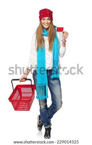 Winter shopping concept. Full length of happy girl in winter hat and scarf showing blank credit card and holding empty shopping basket, on white background - stock photo