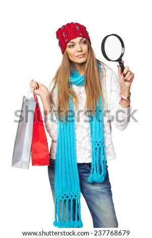 Winter shopping concept. Smiling beautiful woman in winter hat and scarf holding shopping bags and searching through magnifying glass, over white background - stock photo
